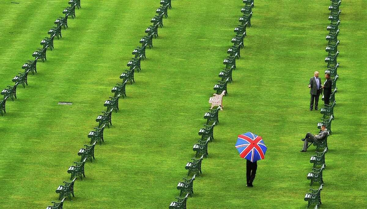 A man with a union jack umbrella walks between the benches at Ascot race course, on the fourth day of the annual Royal Ascot horse racing event near Windsor, Berkshire, west of London.