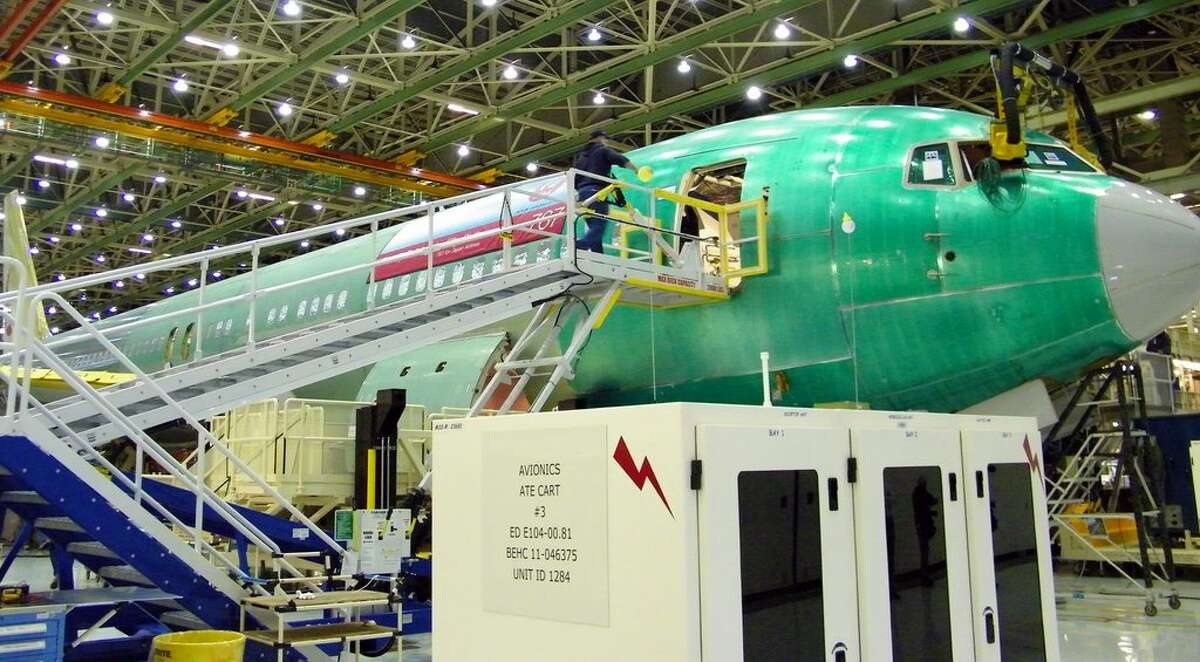 Boeing workers assemble a 767 for Japan Airlines on Thursday, June 2, 2011 in Boeing's wide-body plant in Everett, Wash.