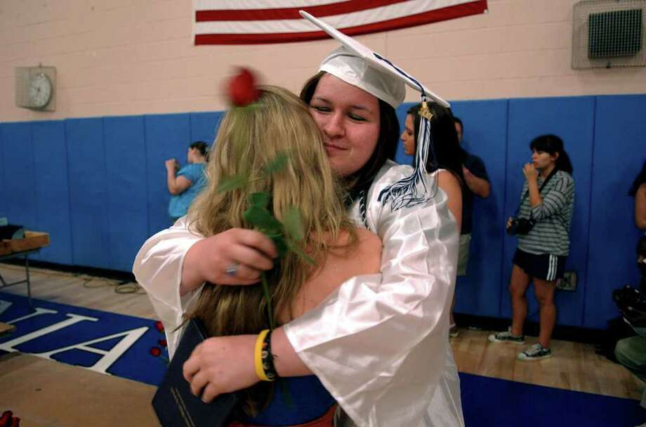 Graduate Amanda Faiella hugs her friend Veronica Devine after getting her diploma, during Ansonia High's Commencement Exercises in Ansonia, Conn. on Thursday June 17, 2011. Photo: Christian Abraham / Connecticut Post
