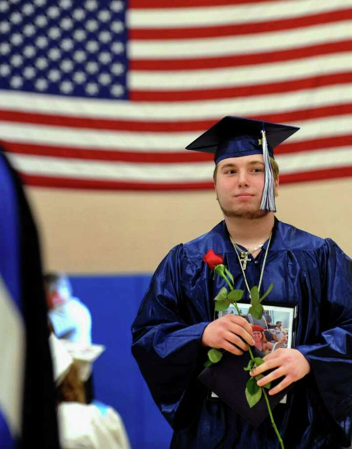 Graduate Albert Minopoli walks back to his seat after getting his diploma, during Ansonia High's Commencement Exercises in Ansonia, Conn. on Thursday June 17, 2011. Around his neck is a photo of his mother Isabella, who passed away. Photo: Christian Abraham / Connecticut Post