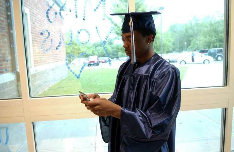 Highlights from Ansonia High School's Commencement Exercises in Ansonia, Conn. on Thursday June 17, 2011. John Haddock texts his mom to see if she's arrived yet. Photo: Christian Abraham / Connecticut Post