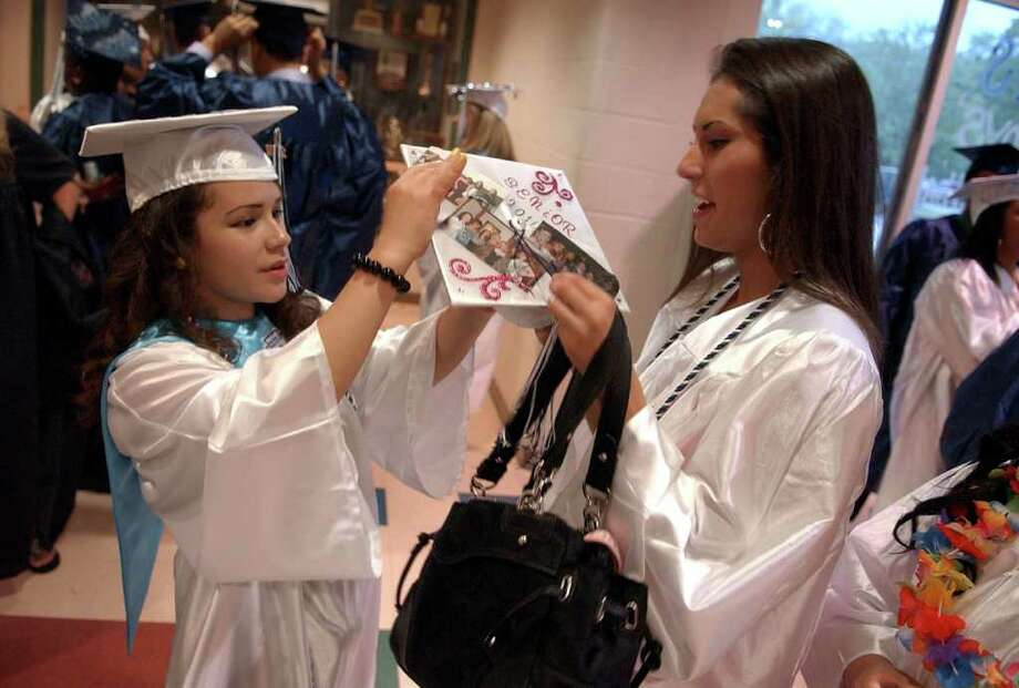 Highlights from Ansonia High School's Commencement Exercises in Ansonia, Conn. on Thursday June 17, 2011. Natalie Caneen, right, gets some help with her cap from classmate Ivette Ulloa before graduation. Photo: Christian Abraham / Connecticut Post