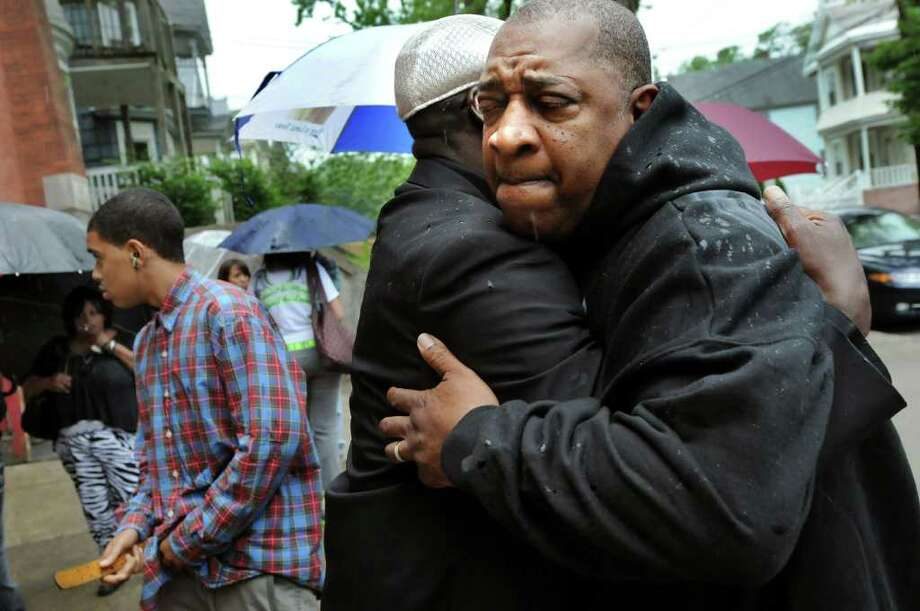 Fred Gentry, Eddie Stanley's great uncle, right, embraces Ro Caldwell outside during June 17, 2011, calling hours at Refreshing Spring Church in Schenectady. Stanley, 15, was killed at a party June 12, 2011. (Cindy Schultz / Times Union) Photo: Cindy Schultz