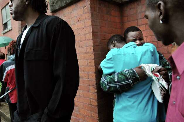 A friend consoles Barkin Tomer, 17, center, as mourners gather to pay their respects to Eddie Stanley, who was killed at a party Sunday, June 12, 2011, on Friday, June 17, 2011, at Refreshing Spring Church in Schenectady. (Cindy Schultz / Times Union) Photo: Cindy Schultz