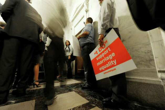 A demonstrator stands in the hallway near the media in the outside of Senate Majority Leader Dean Skelos' office complex in the State Capitol in Albany, N.Y. June 17, 2011, (Skip Dickstein / Times Union) Photo: SKIP DICKSTEIN / 2011