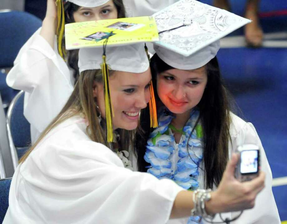 Megan Bingman , and Bianca Bennett take a photo during Brookfield High School's graduation was held at Western Connecticut State University's O'Neill Center in Danbury, Saturday, June 18, 2011. Photo: Michael Duffy / The News-Times