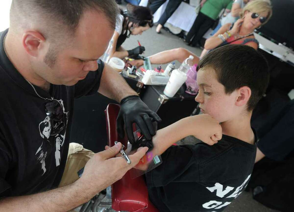 Highlights from the 23rd Annual Fairfield County Irish Festival at Fairfield University in Fairfield, Conn. on Thursday June 18, 2011. The Irish Festival continues on Sunday from noon until 8 PM. Declan O'Donnell, of Fairfield, gets a Daffy Duck airbrush tatoo from Tim Meyer of Fireball Designs.