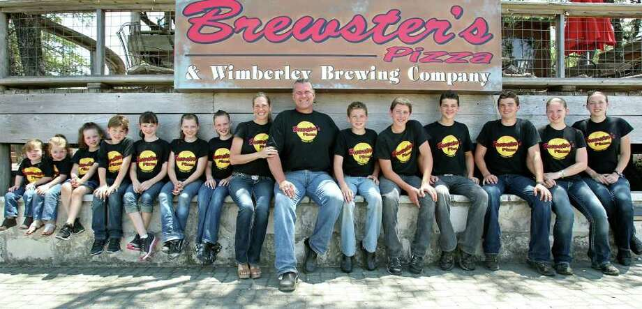 Former San Francisco 49ers offensive lineman Bruce Collie and his family pose at their business — Brewster's Pizza in Wimberley. From left are son Dennison, daughters Jadyn and Daltyn, son Hansen, daughters Hadyn, Calyn and Bergyn, wife Holly, Bruce, sons Cameron, Branson, Denton and Jensen, and daughters Jordyn and Devyn. TOM REEL/treel@express-news.net Photo: TOM REEL, Express-News / © 2011 San Antonio Express-News