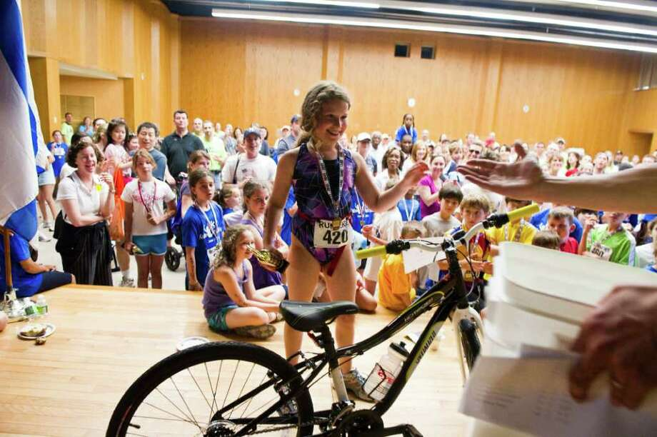 After winning the 7-10 year-old girls division, Rachel Gelfand seals the perfect day winning a new bike from Cycle Center in a raffle as the Stamford Jewish Community Center holds its second annual Kids Triathlon, for children ages 4 to fourteen, on Newfield Avenue in Stamford, Conn., June 18, 2011.  215 kids competed in the event. Photo: Keelin Daly / Stamford Advocate