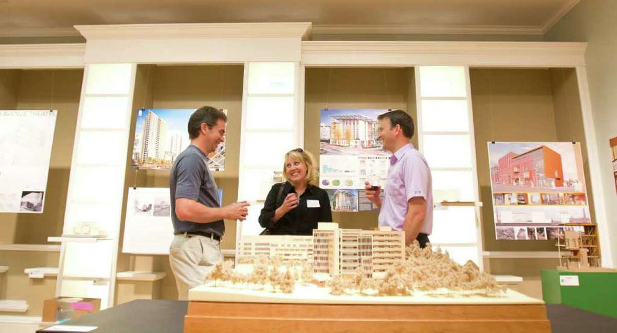 From left to right; Dace Campbell, Lindsey Pflugrath and Niklas Pflugrath talk in front of a model exhibit at the 14th annual Seattle Architecture Foundation Model Exhibit in Seattle on Friday, June 17, 2011.