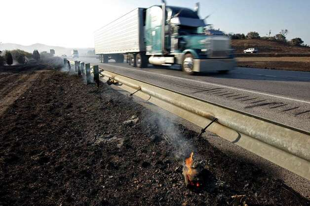 Drivers pass a burned Interstate 10 guardrail near Welfare. Roughly 85 firefighters from volunteer units and the Texas Forest Service fought the fire. Photo: Edward A. Ornelas/eaornelas@express-news.net / © SAN ANTONIO EXPRESS-NEWS (NFS)