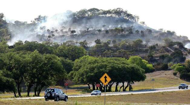 Drivers pass smoldering brush near Welfare from a wildfire that burned 140 acres before it was contained around nightfall. Photo: Edward A. Ornelas/eaornelas@express-news.net / © SAN ANTONIO EXPRESS-NEWS (NFS)