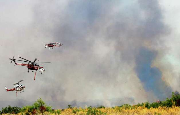 Helicopters leave after replenishing their water supply as they battle ...