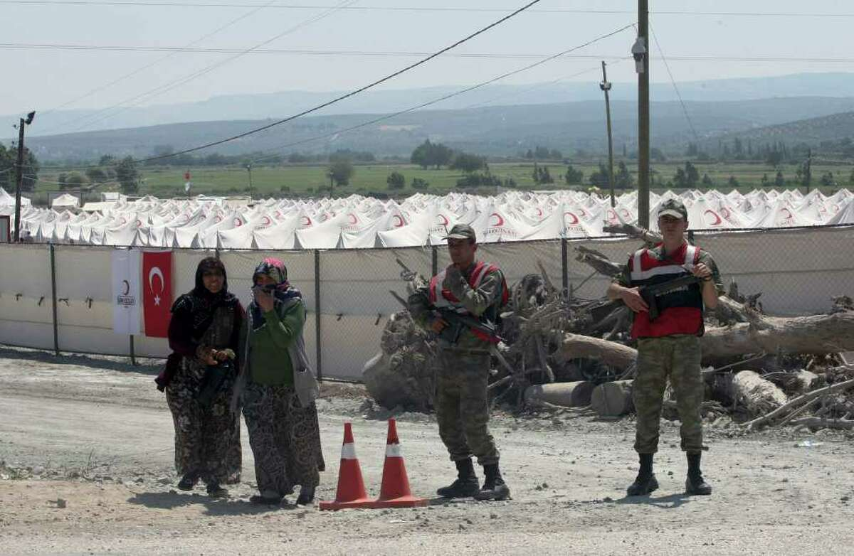 Women pass by Turkish soldiers standing outside a Syrian refugee camp just at the border in Turkey near to the Turkish village of Boynuyogun in Hatay province, Turkey, Friday, June 18, 2011. (AP Photo/Burhan Ozbilici)