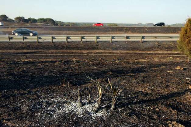 Motorists pass smoldering brush after a wildfire moved through the area off Interstate 10 at Exit 533 near Welfare on Sunday, June 19, 2011. Photo: Edward A. Ornelas/eaornelas@express-news.net / © SAN ANTONIO EXPRESS-NEWS (NFS)