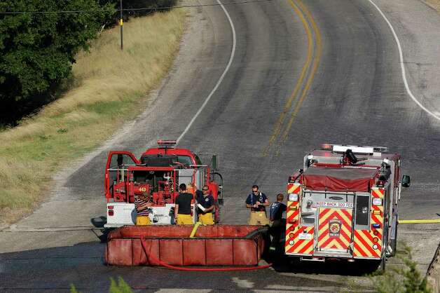 Firefighters work the scene of a wildfire off Interstate 10 at Exit 533 near Welfare on Sunday, June 19, 2011. Photo: Edward A. Ornelas/eaornelas@express-news.net / © SAN ANTONIO EXPRESS-NEWS (NFS)