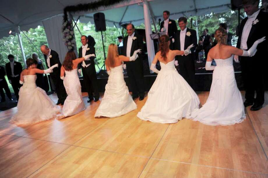 "The debutantes curtsy to their fathers before dancing the  ""Blue Danube"" at the Greenwich Cotillion 2011 presented by the Junior League of Greenwich, at Tomes-Higgins House on Saturday, June 18, 2011. Photo: Helen Neafsey / Greenwich Time"