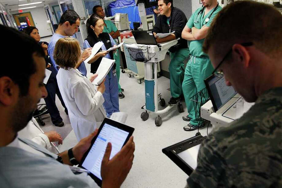Resident Dr. Pedro Pablo Gomez, center top in a black sweater, reads a patient's progress report while using a Computer on Wheels, (COW), at University Hospital, Tuesday, June 14, 2011. He and other residents were making the rounds at the Surgical Intensive Care Unite with University Health System's Dr. Michael. The team uses Computer on Wheels, (COW) and iPads and other personal computers as they make the rounds. JERRY LARA/glara@express-news.net Photo: JERRY LARA, Jerry Lara/Express-News / SAN ANTONIO EXPRESS-NEWS