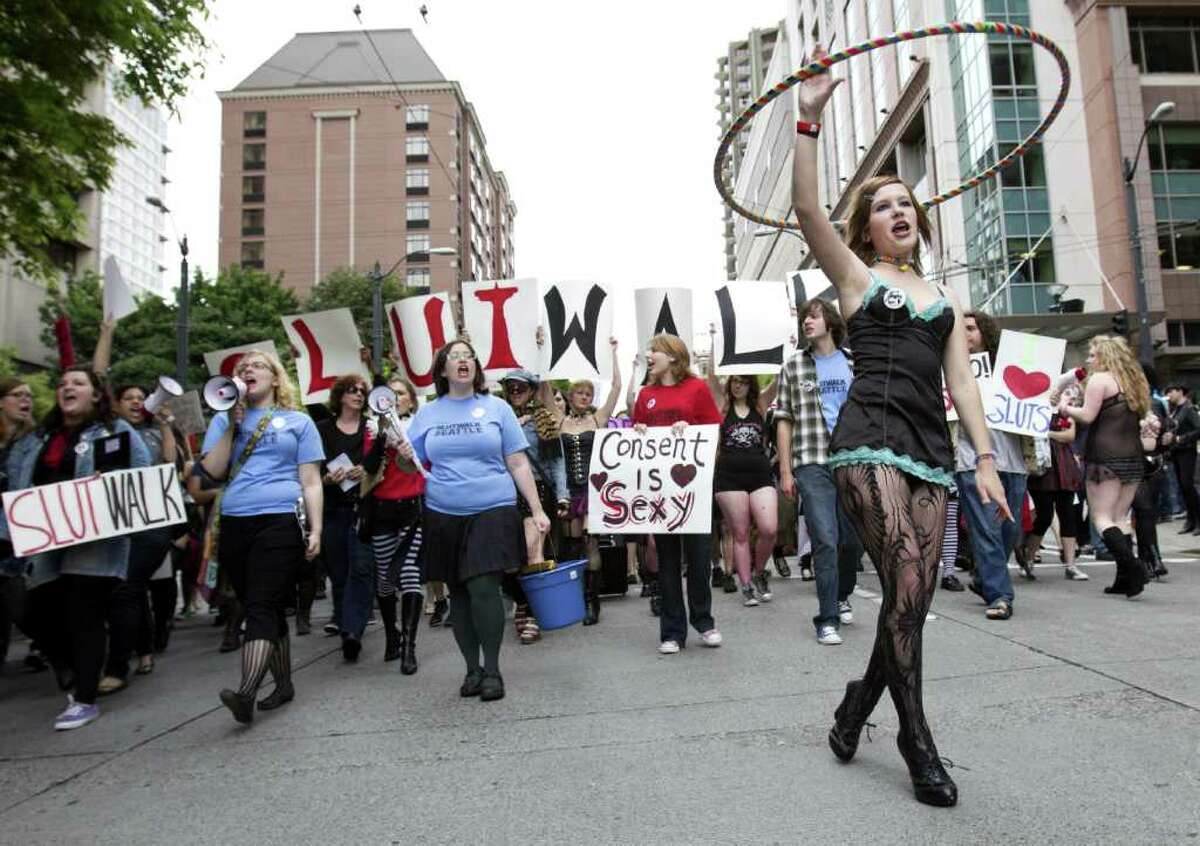 A woman twirls a hula hoop in front of the leading row of the SlutWalk Seattle march on Sunday, June 19, 2011. Demonstrators marched from Cal Anderson Park towards Westlake Center via Pine Street, protesting the practice of blaming victims of sexual assault because of their attire. SlutWalks have been held in numerous cities around the world in response to an incident in which a Canadian police officer said women could better avoid being victims if they would refrain from dressing like sluts.
