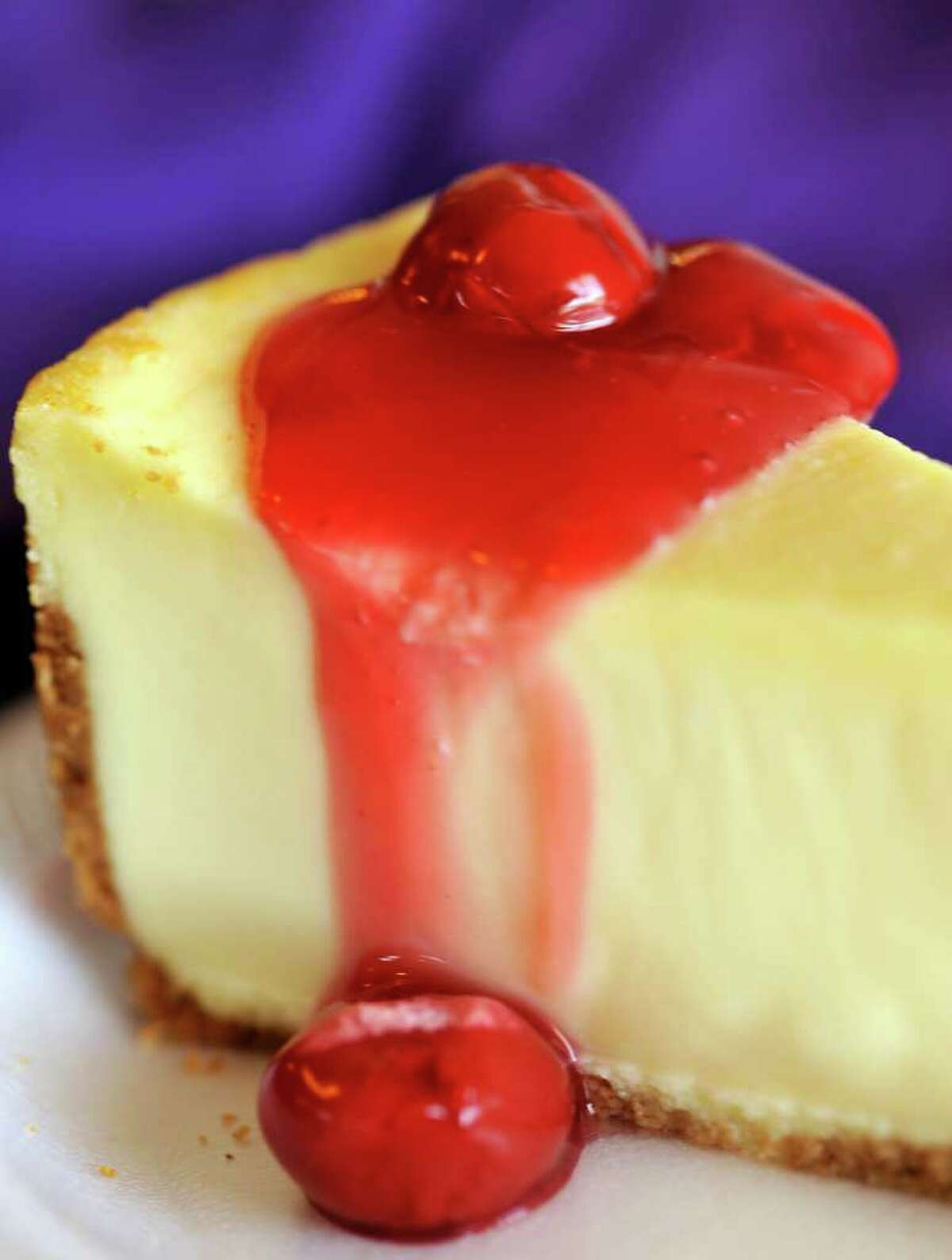 Cheesecake is topped with cherry drizzle.