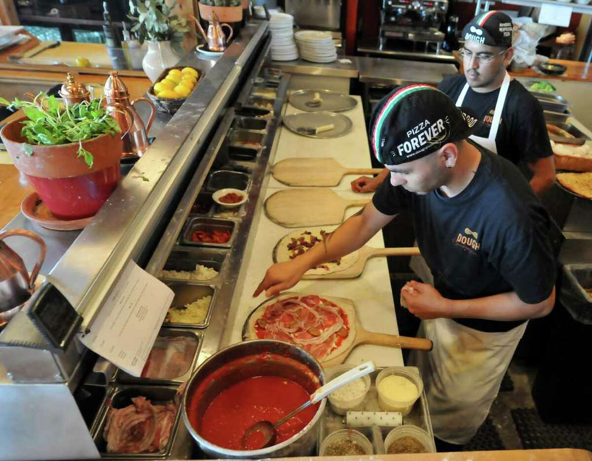 Michael Brito (left) and Jose Padron prepare pizza's at Dough Pizzeria Napoletana, voted best non-chain pizza by both the readers and critics.