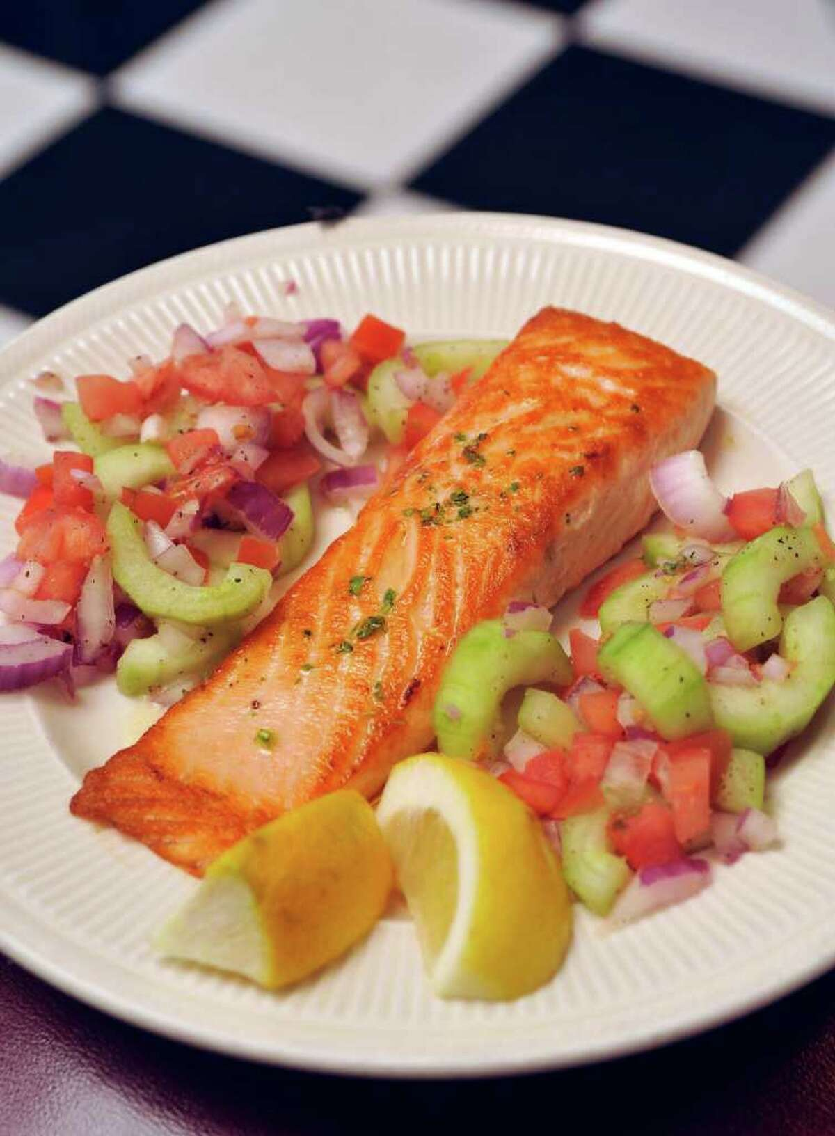 The grilled salmon, topped with lemon and butter, is a favorite of Checkers Diner owner Marlen Ramirez.