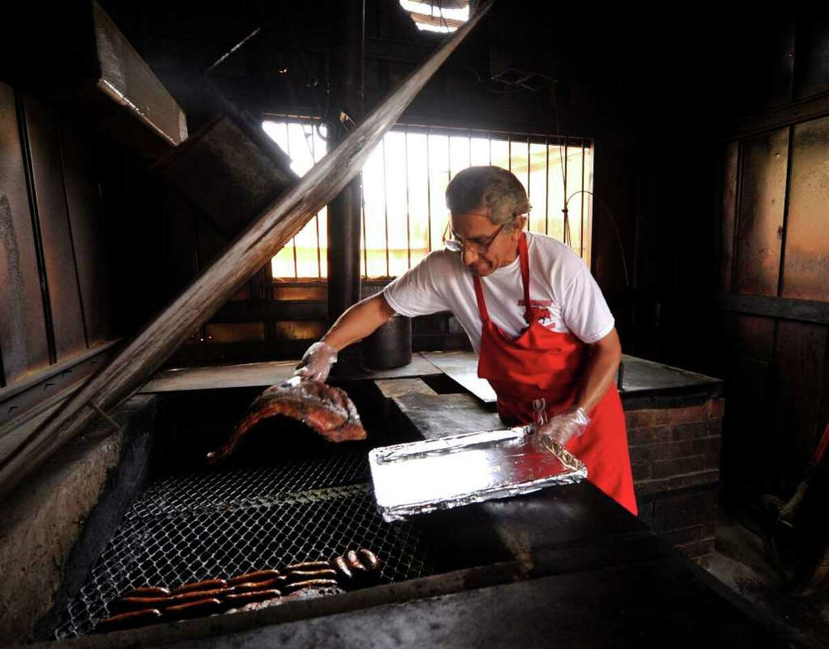 Javier Sanchez, pitmaster at Rusty Bucket BBQ, pulls some ribs off the smoker. The restaurant, at 600 Cupples Rd., was the Critics' Choice for best ribs in San Antonio.