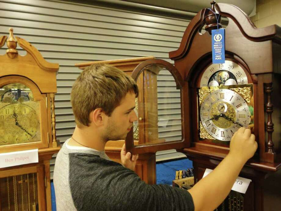 David Pittera, 18, sets the time on the grandfather clock he made as one of his senior projects at Fairfield Warde High School. Pittera won Best in Show, Advanced Woodworking Award, for his clock at the annual woodworking show at the school. Photo: Meg Barone / Fairfield Citizen freelance
