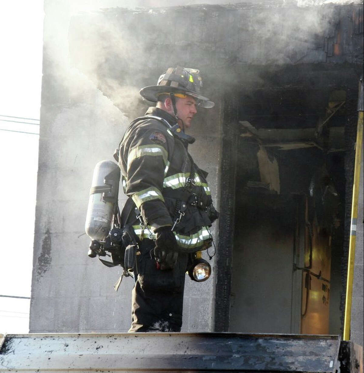 A Fairfield firefighter battles a blaze that broke out on Sunday, June 19, 2011 at a second-floor apartment upstairs from the Bejing chinese restaurant in Fairfield, Conn.