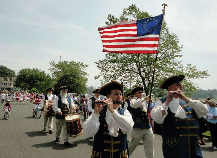 Pipers beneath Old Glory in Saturday's parade through Southport Village before the annual Blessing of the Fleet ceremony. Photo: Meg Barone / Fairfield Citizen freelance