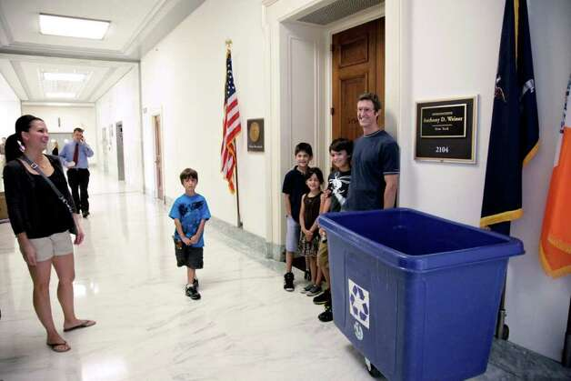 On a family vacation in the nation's capital, David Whitmer, far right, of Orlando, Fla., stops for a souvenir photo outside the office of departing Rep. Anthony Weiner, D-N.Y., on Capitol Hill in Washington, Monday, June 20, 2011.  Weiner announced his resignation last week following revelations that he sent text messages containing sexually suggestive photos of himself to young women. (AP Photo/J. Scott Applewhite) Photo: J. Scott Applewhite