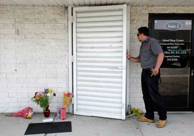 An employee of a trauma and crime scene cleaning crew talks to police inside the pharmacy where four people were killed in a shooting in Medford, N.Y., Monday, June 20, 2011.   (AP Photo/Seth Wenig) Photo: Seth Wenig