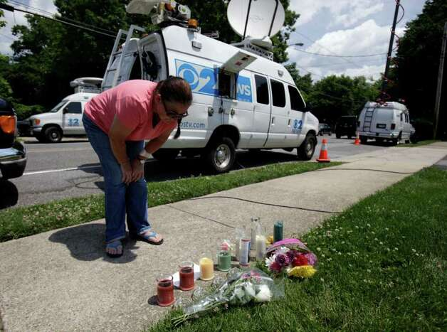 A woman, who did not wish to be identified, looks at a small memorial to one of the victims in a shooting near the pharmacy where the shootings occurred in Medford, N.Y., Monday, June 20, 2011.   (AP Photo/Seth Wenig) Photo: Seth Wenig
