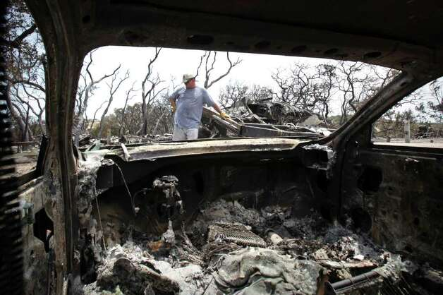 Andy Skelton takes a break from picking through the remains of his parent's RV home that was destroyed, as well as thier car, in a brush fire at Top of the Hill RV Resort  just outside Boerne, TX, Monday, June 20, 2011. Photo Bob Owen/rowen@express-news.net Photo: Bob Owen, Bob Owen/Express-News / rowen@express-news.net