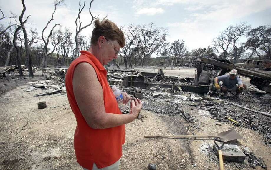 Sue Skelton inspects a family ring as her son Andy Skelton, right, searches for other family heirlooms as they pick through the remains of their RV home that was destroyed in a brush fire at Top of the Hill RV Resort just outside Boerne, TX, Monday, June 20, 2011. Photo Bob Owen/rowen@express-news.net Photo: Bob Owen/Express-News