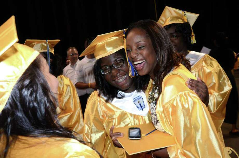 Marie Petit-Homme cheerfully hugs fellow graduate Samrash Brown during the 2011 Warren Harding High School Commencement at Webster Bank Arena in Bridgeport on Monday, June 20, 2011. Photo: Amy Mortensen / Connecticut Post Freelance