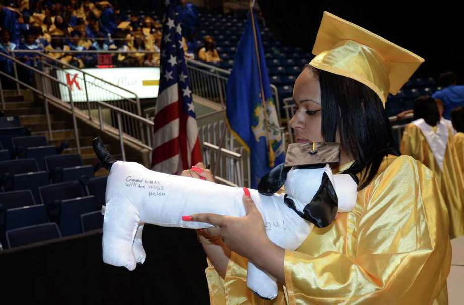 Mataya Robertson signs graduate Rafael Parussolo's stuffed dog during the 2011 Warren Harding High School Commencement at Webster Bank Arena in Bridgeport on Monday, June 20, 2011. Photo: Amy Mortensen / Connecticut Post Freelance