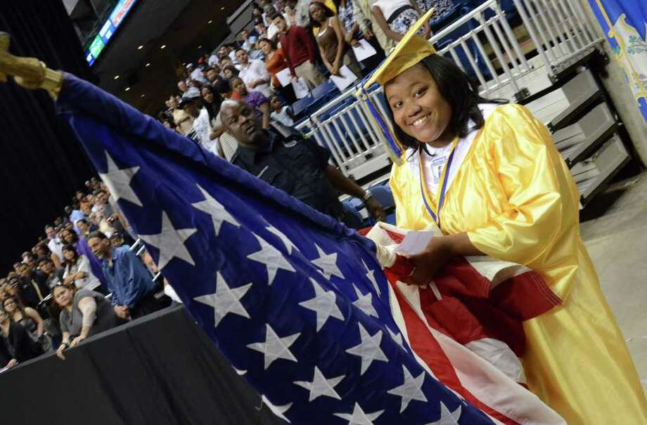 Tashilyana Seales Shuler-Drakes carries the flag during the 2011 Warren Harding High School Commencement at Webster Bank Arena in Bridgeport on Monday, June 20, 2011. Photo: Amy Mortensen / Connecticut Post Freelance