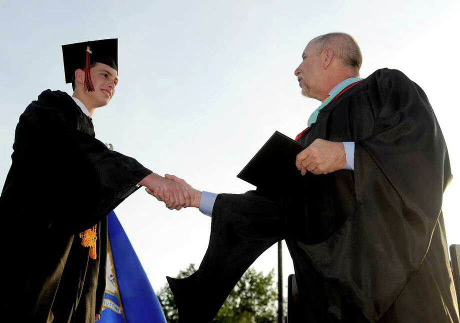 Ryan Brennan is presented his diploma by Superintendent Freeman Burr during the Shelton High School graduation ceremony on Monday, June 20, 2011. Photo: Lindsay Niegelberg / Connecticut Post