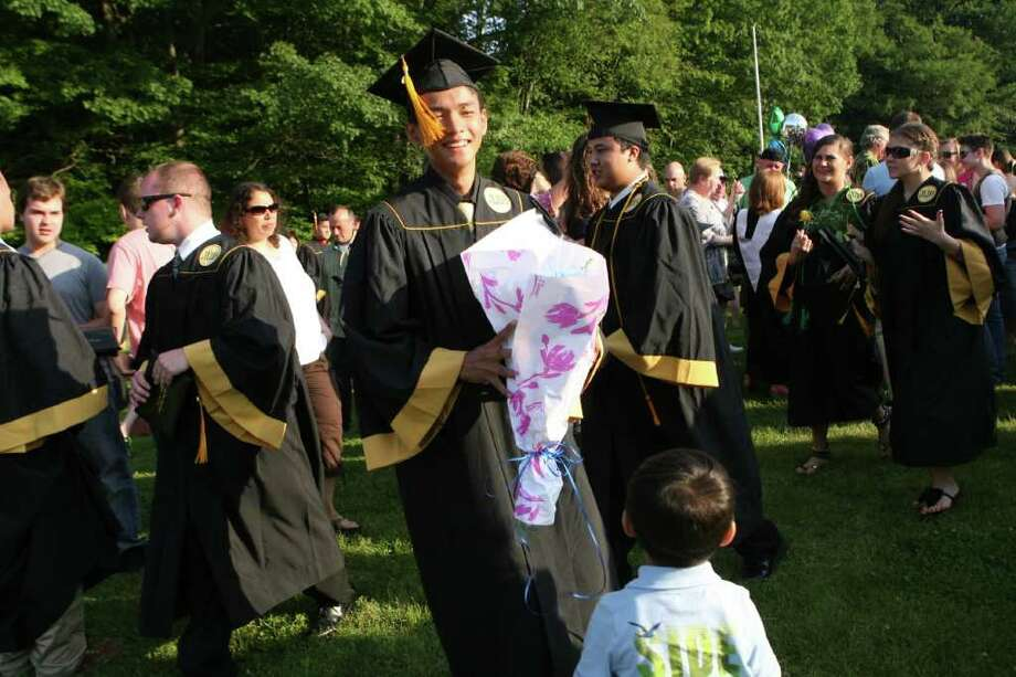 Graduate SokHouth Chay recieves flowers from his nephew, Ryan Chay, 4, at the Jonathan Law High School Commencement ceremony in Milford on Monday, June, 20, 2011. Photo: B.K. Angeletti / Connecticut Post