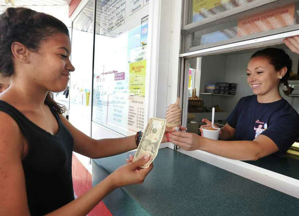 Aja Evans of South Colonie buys some ice cream from Megan Dayton of Troy at the Snowman ice cream shop in Troy, N.Y. Monday June 20, 2011. Aja, who will be a senior in high school next year, works at Fresh Market in Latham. Megan, 22, is UAlbany student and has been working at the Snowman in the summer since she was 22. (Lori Van Buren / Times Union)
