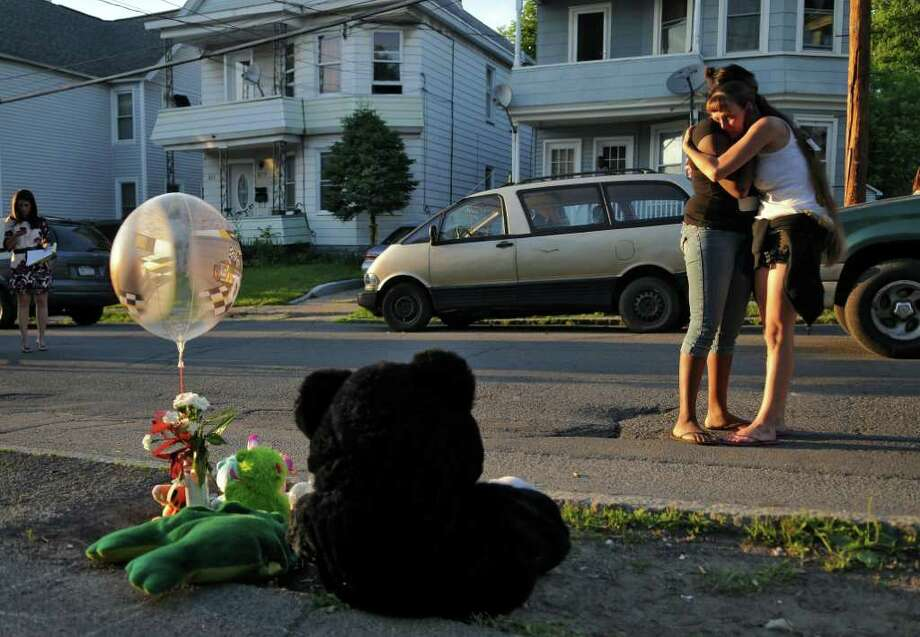 Jamie Darrel, right, is comforted by her friend Quanisha Thomason, left, in front of a Hattie Street sidewalk memorial to Jamie's 20 month old son whose Sunday death was ruled a homicide, on Monday night June 20, 2011 in Schenectady, NY. Jamie lives in the building in the background, second from left with tree in front of porch.  ( Philip Kamrass / Times Union) Photo: Philip Kamrass / 00013643A