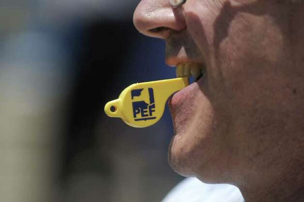 A state worker uses a whistle to make noise  during a rally by state workers outside the capitol on Monday afternoon, June 20, 2011 in Albany.   According to the Public Employees Federation union, state workers at 13 locations around the state held rallies on Monday.  The unionized workers were calling on the Governor to negotiate with them and to not layoff workers.  (Paul Buckowski / Times Union) Photo: Paul Buckowski / 00013627A