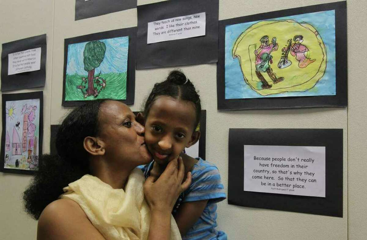 Misgina Hagos,7, (right) gets a kiss from her mother Rahaset Kidane (left) at the Children's Art Celebration held by Catholic Charities Refugee Services in recognition of World Refugee Day 2011. In honor of the day, both refugee children and American children were asked to create original art expressing their views. Hagos and Kidane are from Eritrea and Hagos drew the artwork (upper right) of people playing guitars. (Monday June 20, 2011) JOHN DAVENPORT/jdavenport@express-news.net