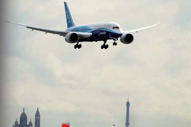 A Boeing 787 Dreamliner prepares to land at Le Bourget airport, as the Sacre Coeur, back left, and the Eiffel Tower are seen in the background, during the Dreamliner's first presentation at the 49th Paris Air Show, Le Bourget, east of Paris, Tuesday, June 21, 2011. Photo: Francois Mori, AP / AP