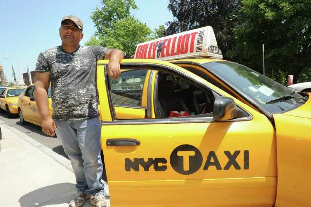 Cab driver Khalid Usmani of NYC stands with his cab parked outside the Capitol in Albany, N.Y. Tuesday  June 21, 2011.  Taxicab drivers descended on the Capitol on Tuesday to protest a bill that would expand ?street hail? rights and authorize the sale of 1,500 additional taxi medallions. (Lori Van Buren / Times Union) Photo: Lori Van Buren