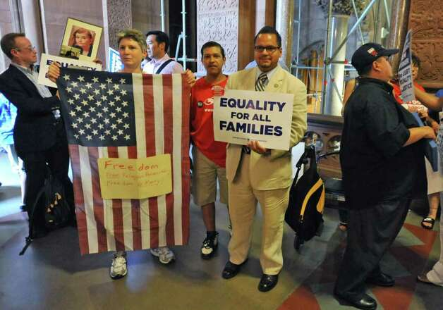 NYS Senator Jose Serrano, middle, holds a sign with supporters for same sex marriage at the Capitol in Albany, N.Y. Tuesday  June 21, 2011.  (Lori Van Buren / Times Union) Photo: Lori Van Buren