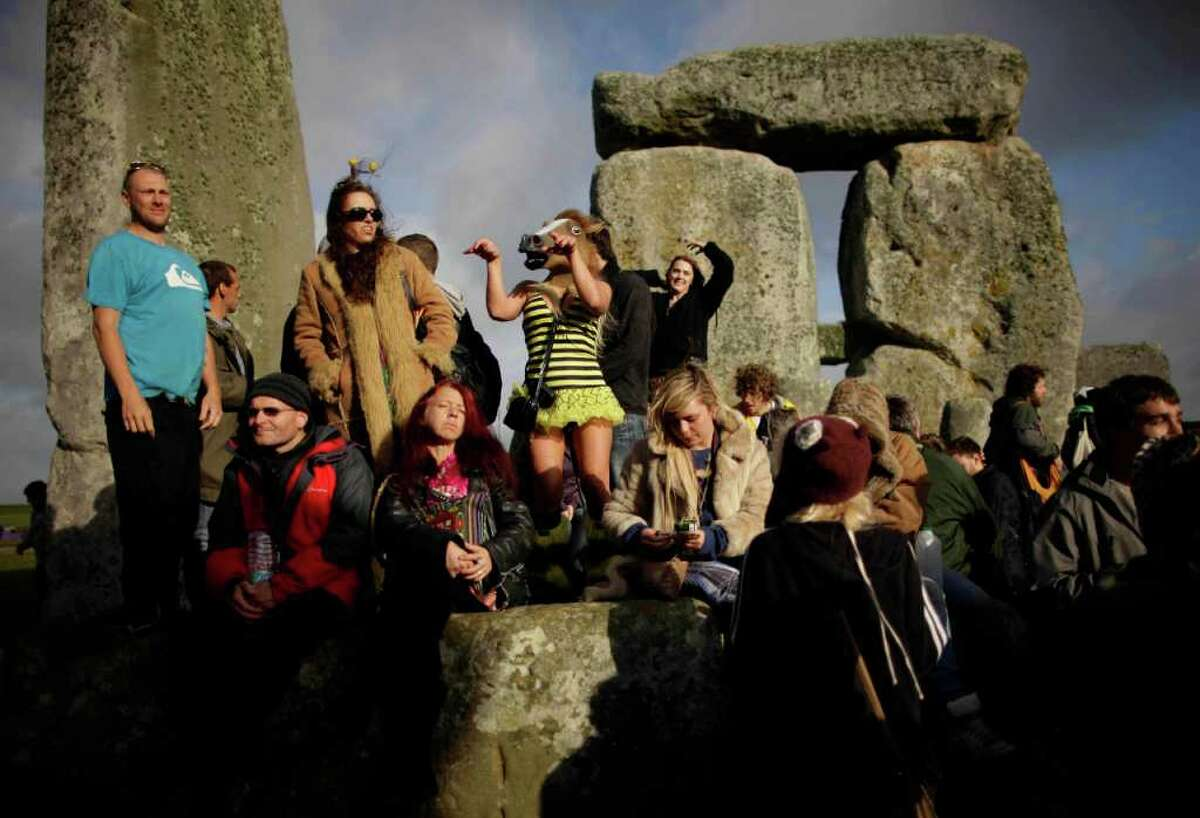 A reveler wearing a horse mask dances during the Summer Solstice at Stonehenge on June 21, 2011.