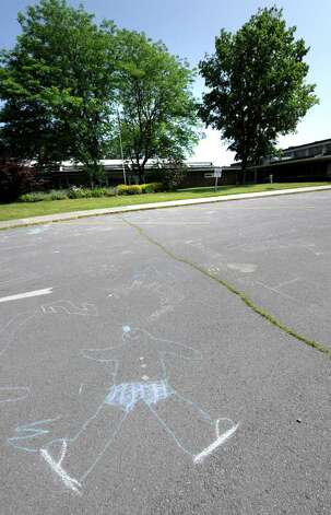 A child's caricature with chalk remains in the parking lot on the last day of  school at the Clarksville Elementary School in Clarksville, N.Y., on June 21, 2011.  The Clarksville Elementary School will close for good after this school year.  (Skip Dickstein/ Times Union) Photo: Skip Dickstein