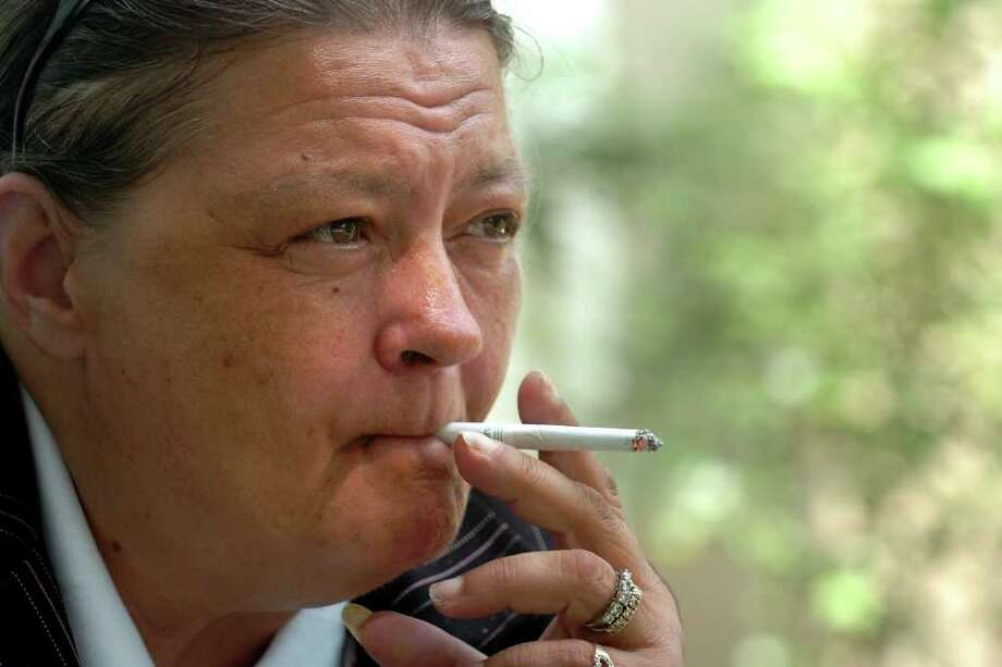 Cathy Santossio, of Ansonia, smokes a cigarette during a break from work in Bridgeport, Conn. June 21st, 2011. Photo: Ned Gerard / Connecticut Post